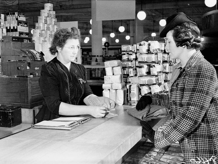 Buying food at the Eaton's department store using ration coupons. Toronto, Canada.